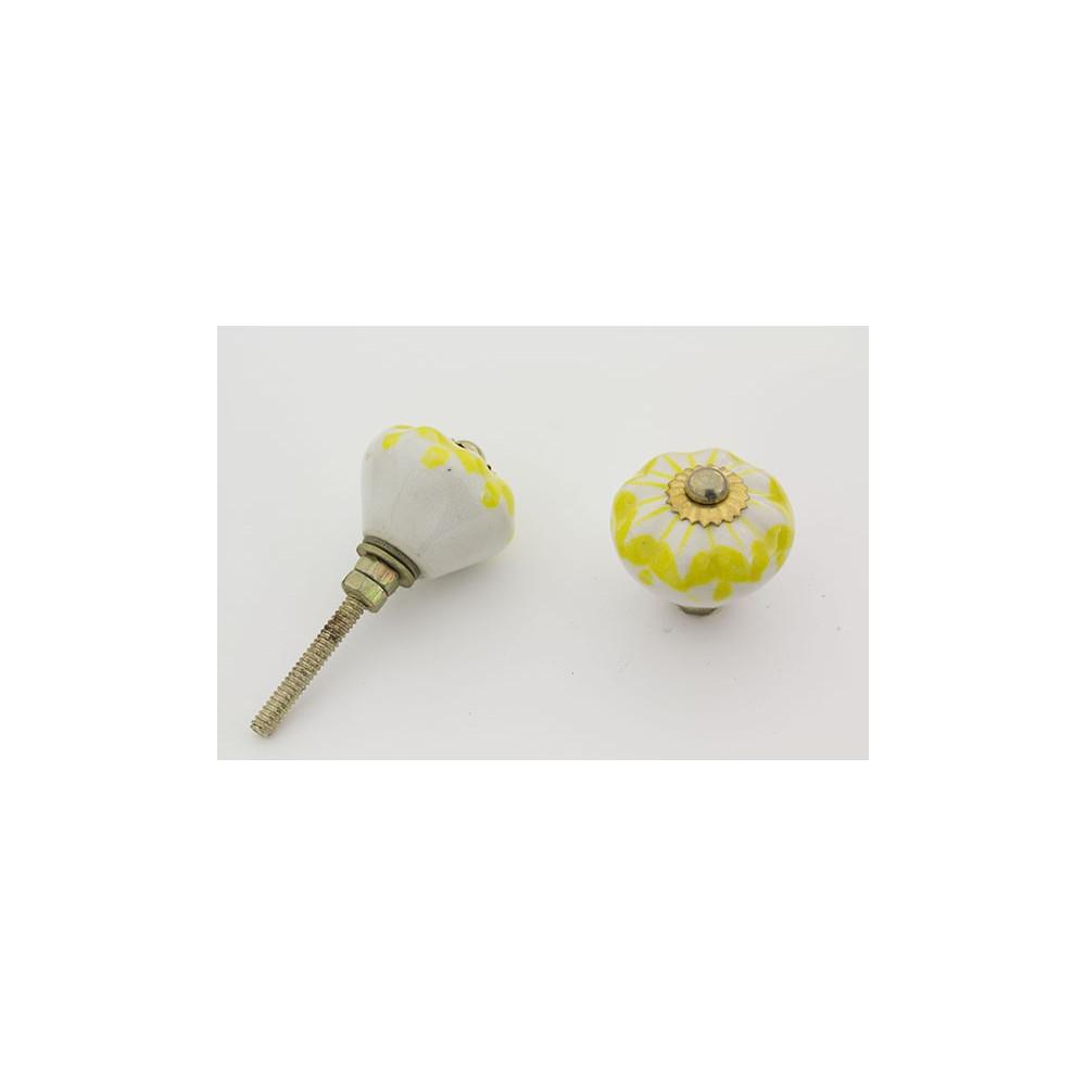Hvid porcelænsknop med gul mønster.